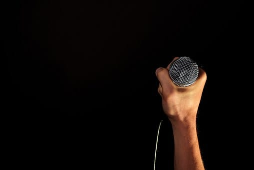 Microphone held by hand with dark background